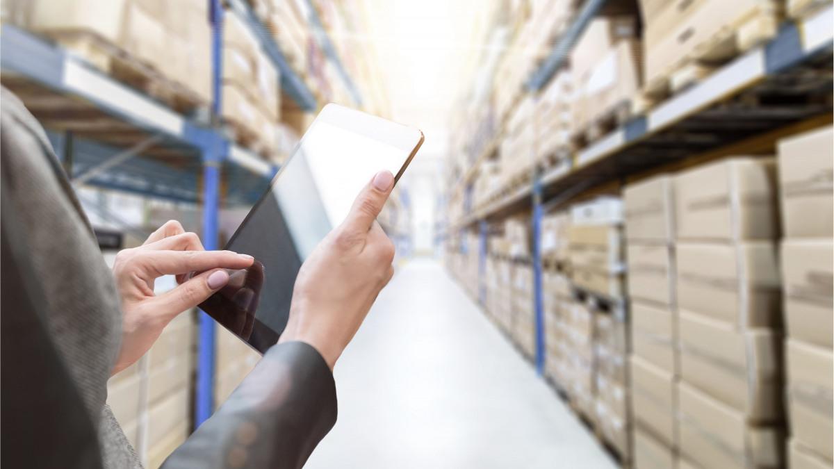 Dipendente addetto al magazzino passa attraverso il capannone con un tablet