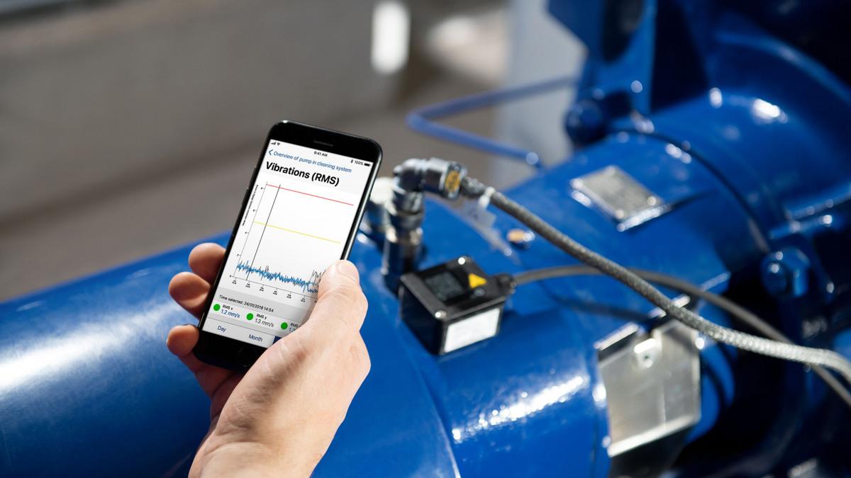 La mano tiene il cellulare, sul display è raffigurato un grafico. Sullo sfondo la pompa KSB con KSB Guard installato.