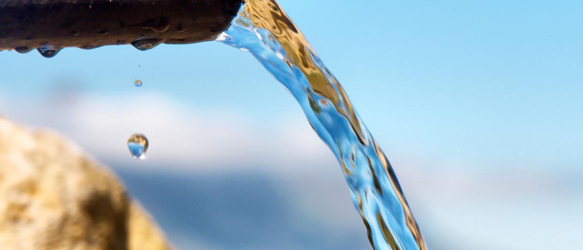Klart vatten flyter genom ett rör i ett vattendrag