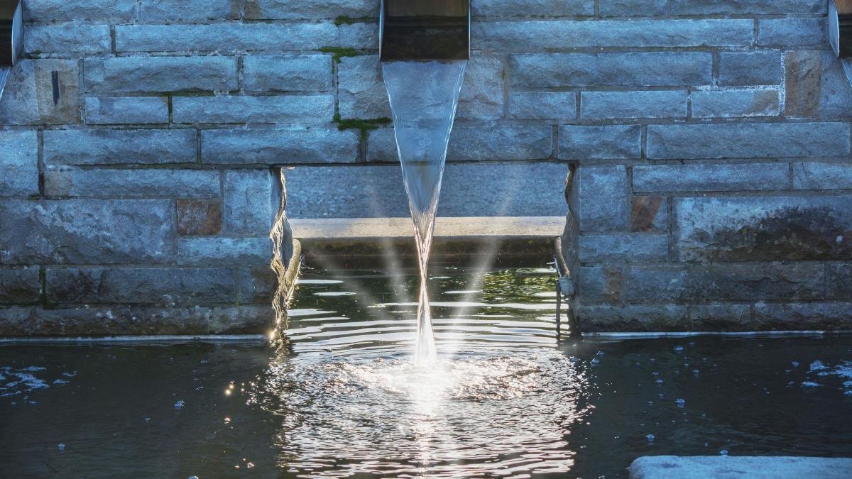 Klart vatten flyter genom ett schakt i en bassäng