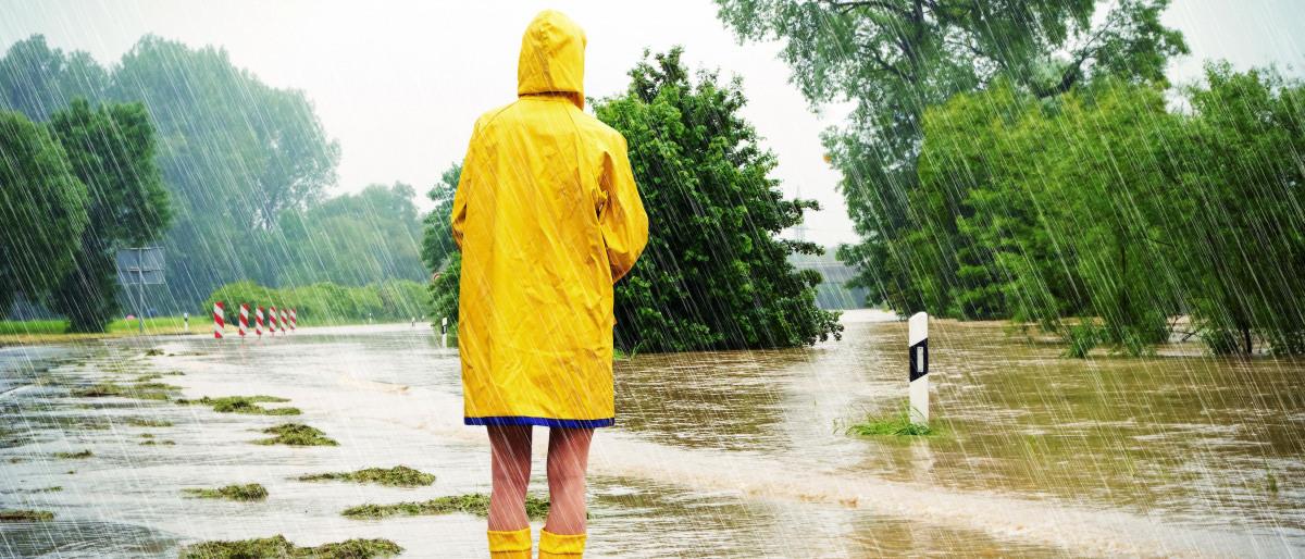 Oseba v dežnem plašču na poplavljeni cesti