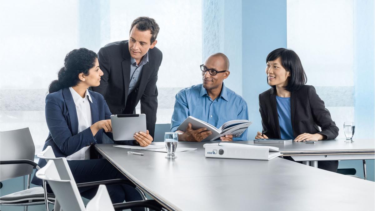 Štirje sodelavci pri pogovoru v pisarni