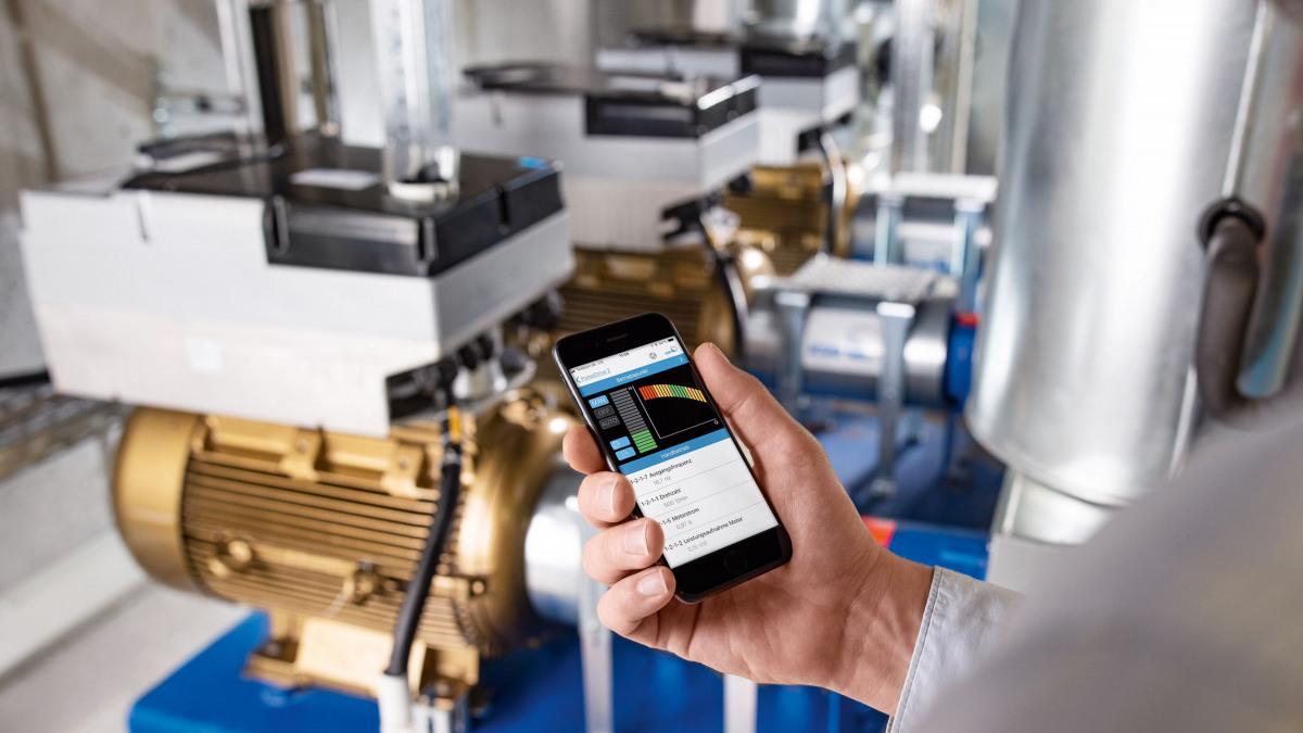 Hand mit iPhone, auf dem Display KSB Flow Manager zur Steuerung von PumpDrive2, im Hintergrund Etanorm-Pumpen mit PumpDrive2