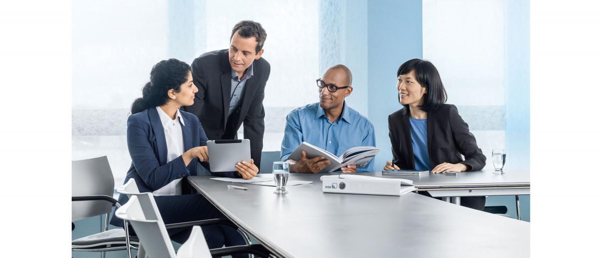 Vier collega's in gesprek op kantoor