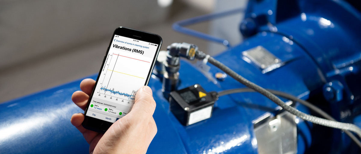 Hand holding a mobile phone with a graph displayed on the screen. In the background is a KSB pump with installed KSB Guard.