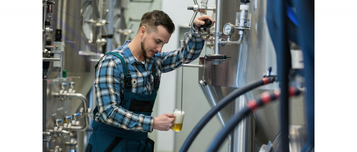 A brewer taking a test sample