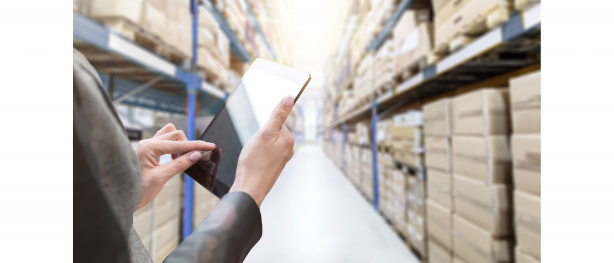 Warehouse employee walking through the warehouse with a tablet