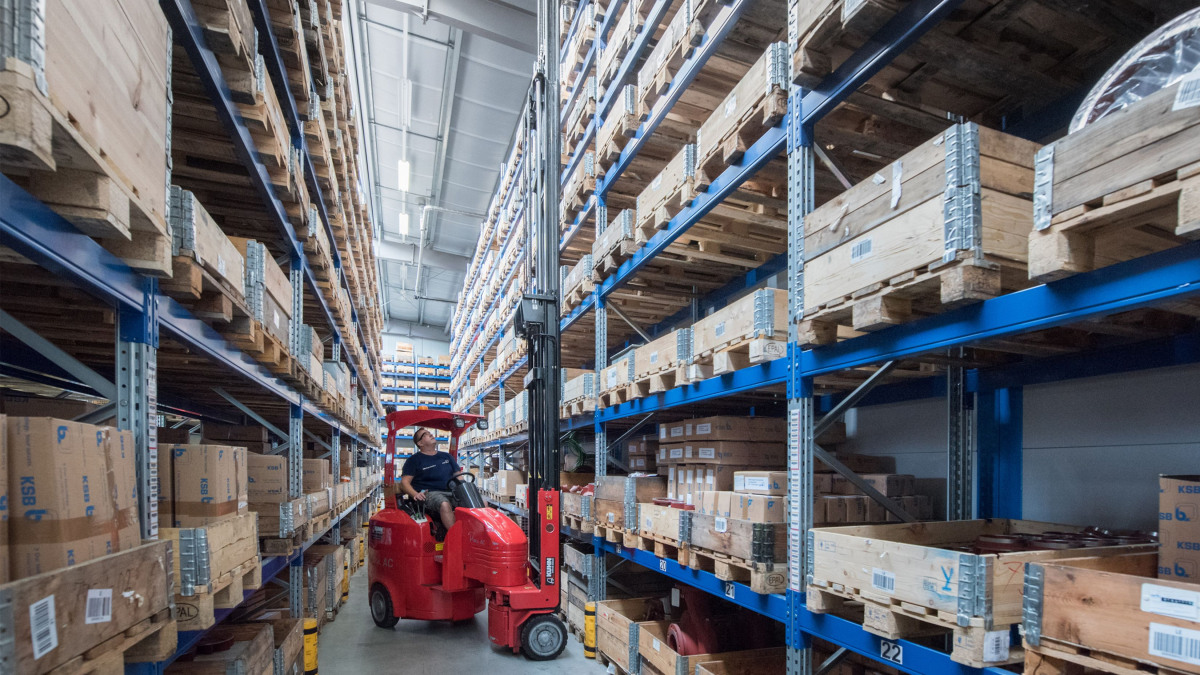 Forklift truck between two rows of high-bay shelving