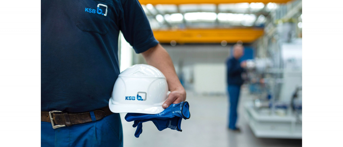 KSB employee holding a hard hat and gloves