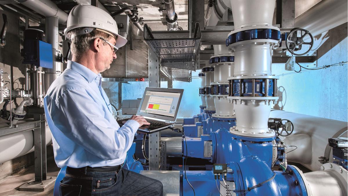 Ingénieur avec ordinateur portable devant une pompe