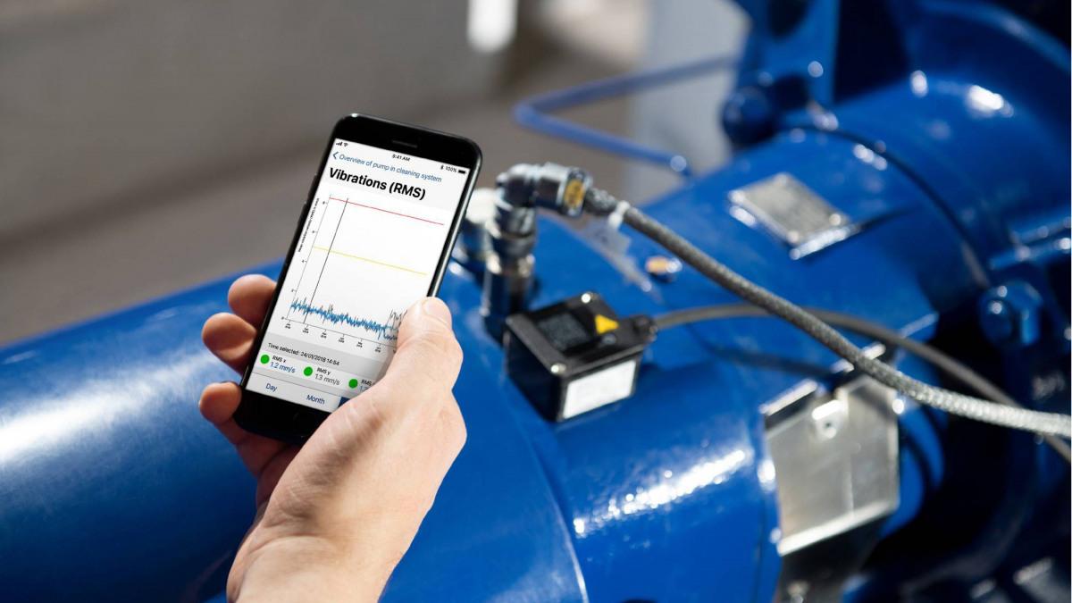 Smartphone dans une main avec une application pour l'analyse de la pompe