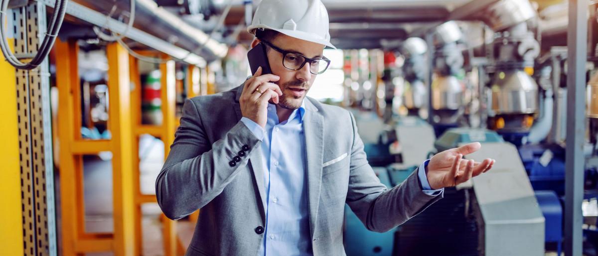 Ein Ingenieur telefoniert mit Smarphone in einem Kraftwerk