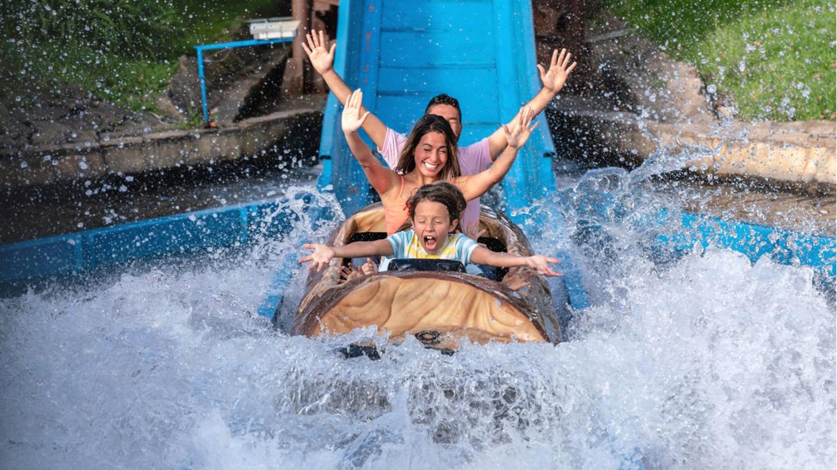Eine Familie fährt in einer Wildwasserbahn. Das Wasser spritzt.