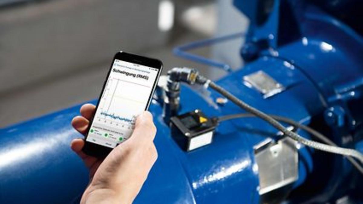 Hand hält Handy, auf dessen Display ein Graf abgebildet ist. Im Hintergrund KSB Pumpe mit installiertem KSB Guard.