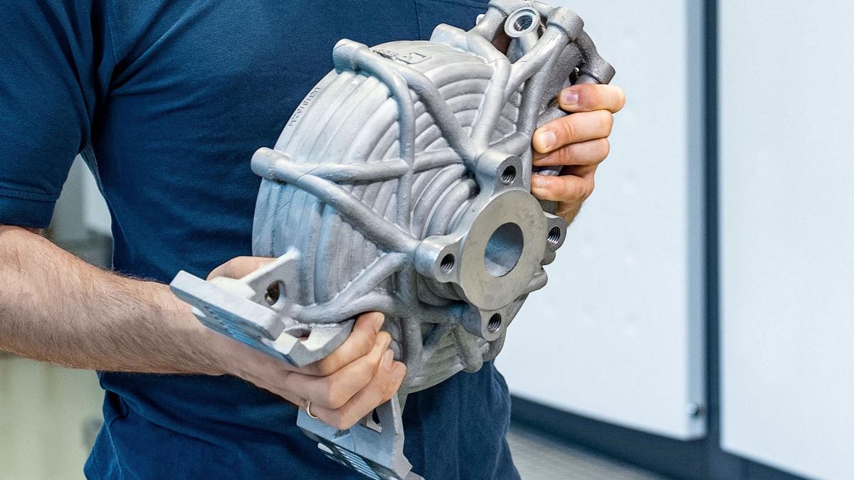 Ein KSB Mitarbeiter hält ein Pumpengehäuse mit integrierten Heizkanälen in seinen Händen.