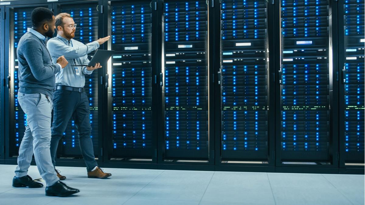 Deux spécialistes informatiques, l'un avec un portable dans les mains, inspectent une série de racks de serveur.