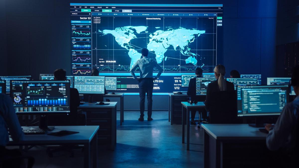 Ein Mann steht vor einer Weltkarte in einem Raum voller Mitarbeiter an Rechnern.