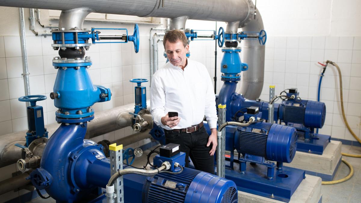 Mann mit Smartphone vor Rohrleitungen, Pumpen und Sensoreinheit