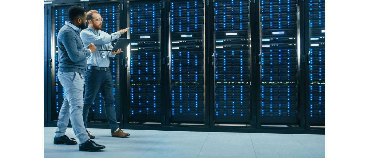 Due professionisti IT, uno con il laptop in mano, esaminano una fila di rack per server.