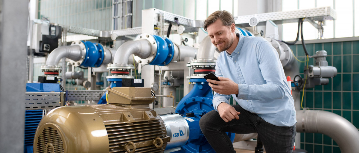 Un collaborateur du Service KSB lit des données numériques sur son smartphone.