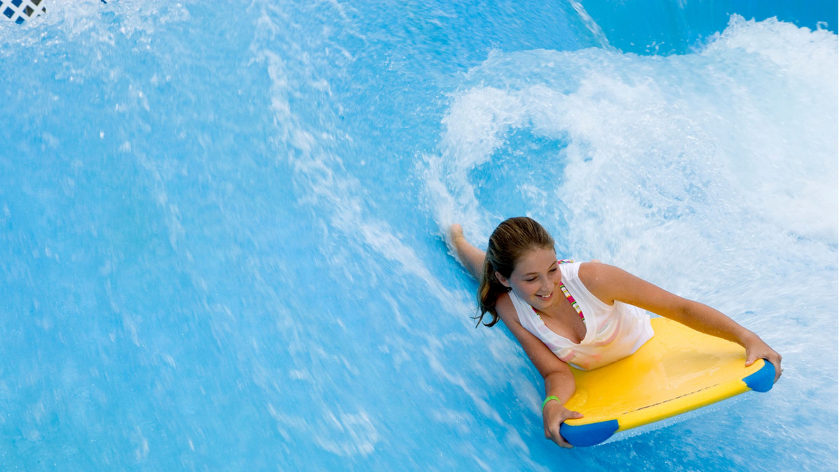 A woman surfs lying down in a surf wave pool.