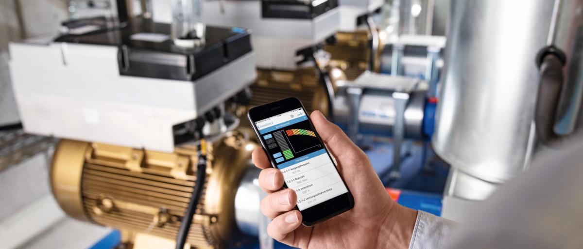 Pantalla de teléfono móvil con la aplicación FlowManager de KSB delante de la bomba configurada