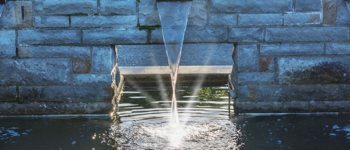 Klares Wasser fließt durch einen Schacht in ein Becken