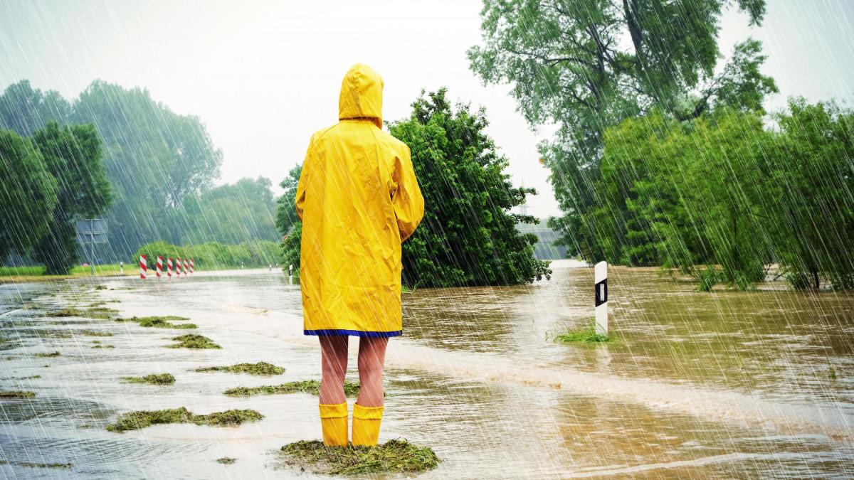 Mann im Regenmantel auf überfluteter Straße