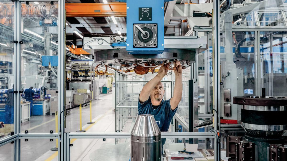 Ein KSB-Mitarbeiter im Werk Halle arbeitet an der Motoren-Wicklung für Tauchmotorpumpen.