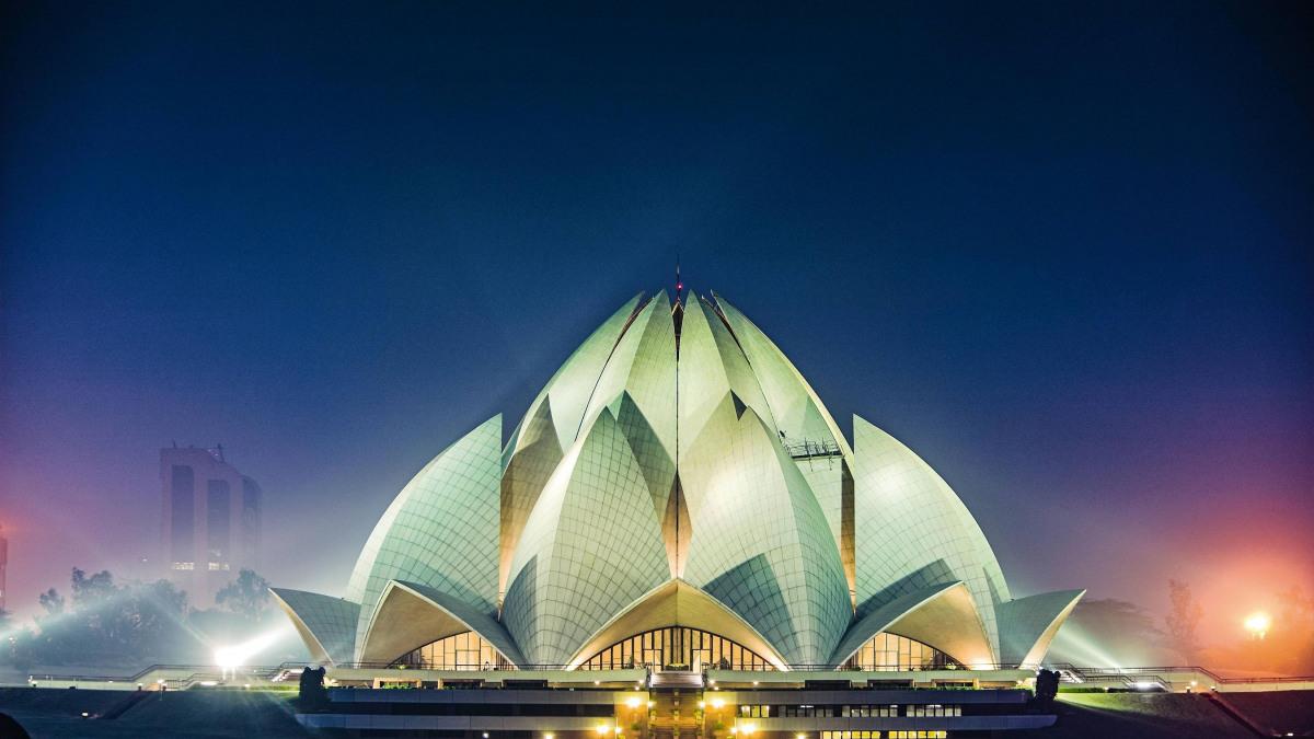 The Lotus Temple in New Delhi, India, is illuminated at night.