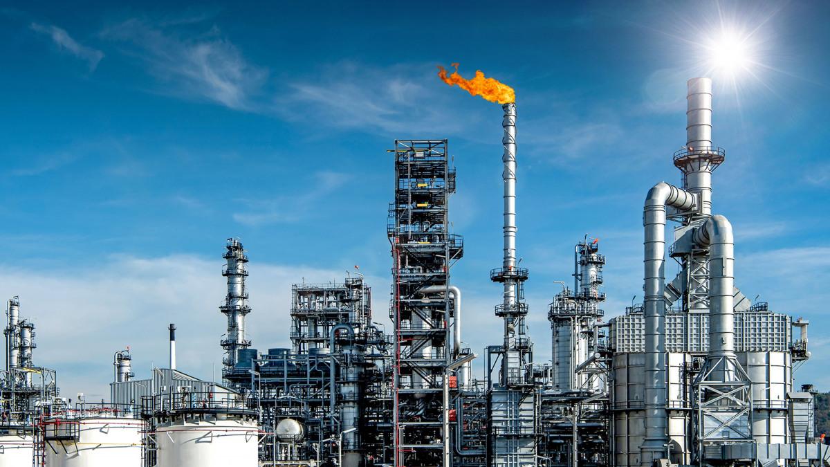 Großer Erdölraffineriekomplex mit orangefarbener Fackel inmitten eines strahlend blauen Himmels