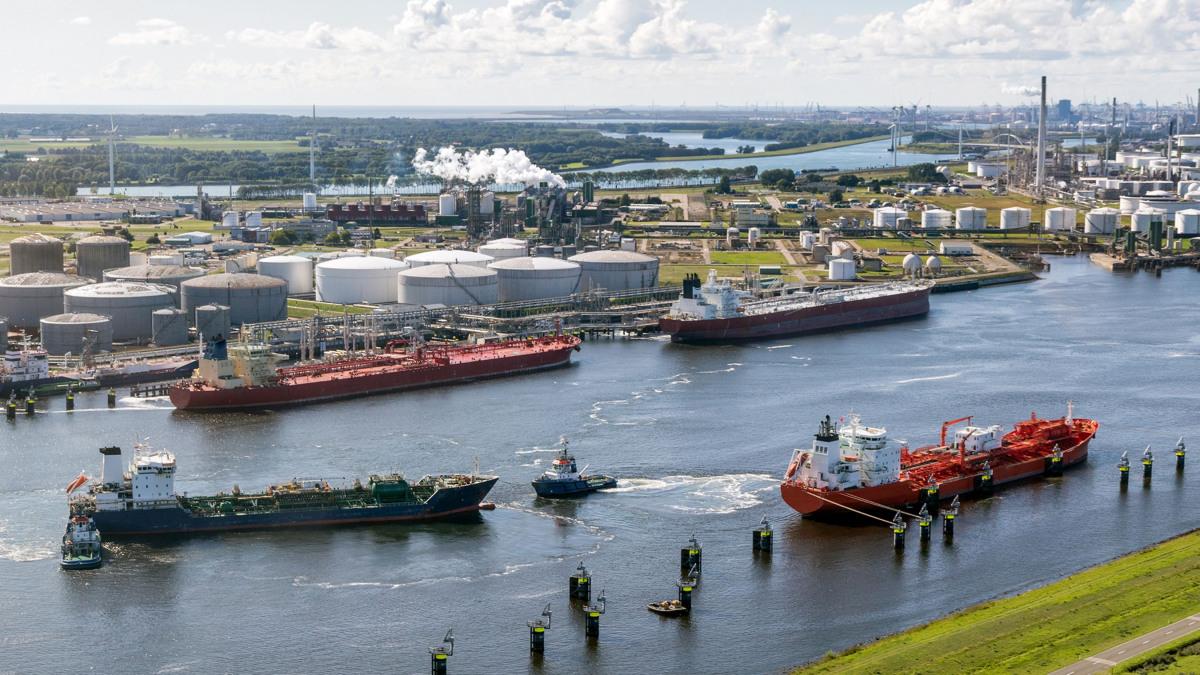 Zwei Tanker auf einem Fluss bereiten sich zum Andocken an eine große Raffinerie vor