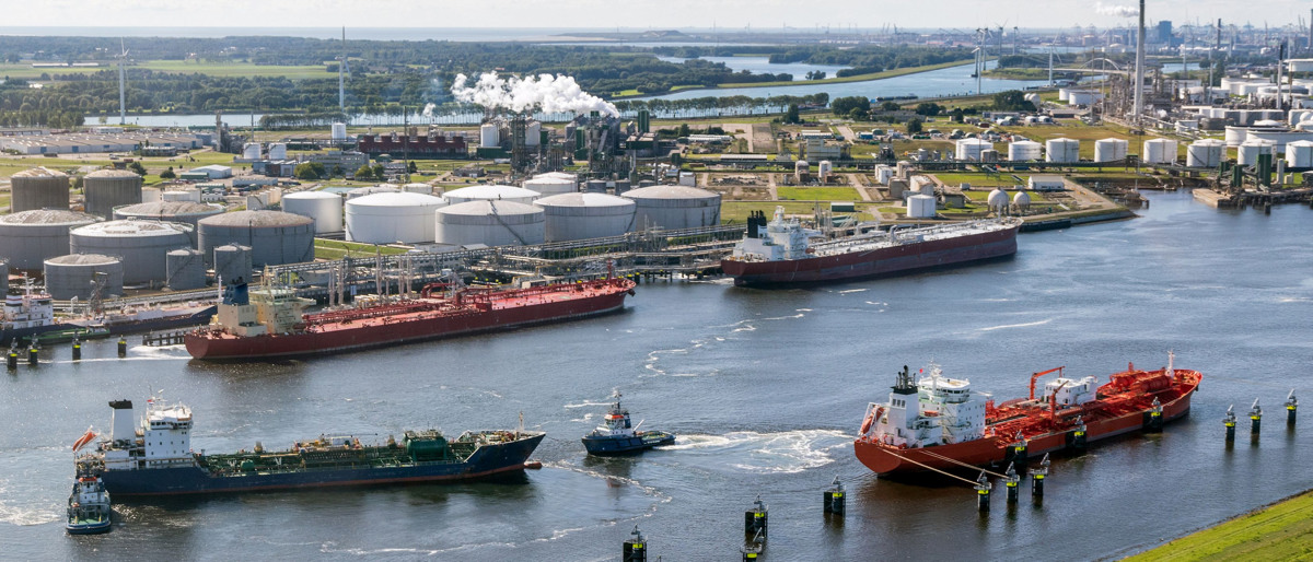 Two barges on a river preparing to dock at a large refinery