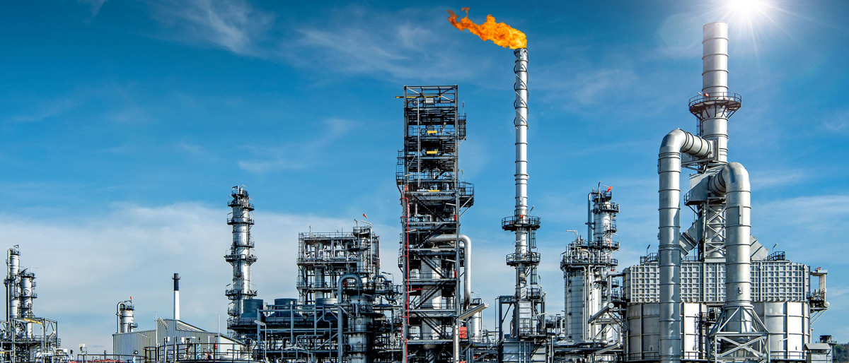 Large oil refinery complex with an orange flare at the centre set against a bright blue sky