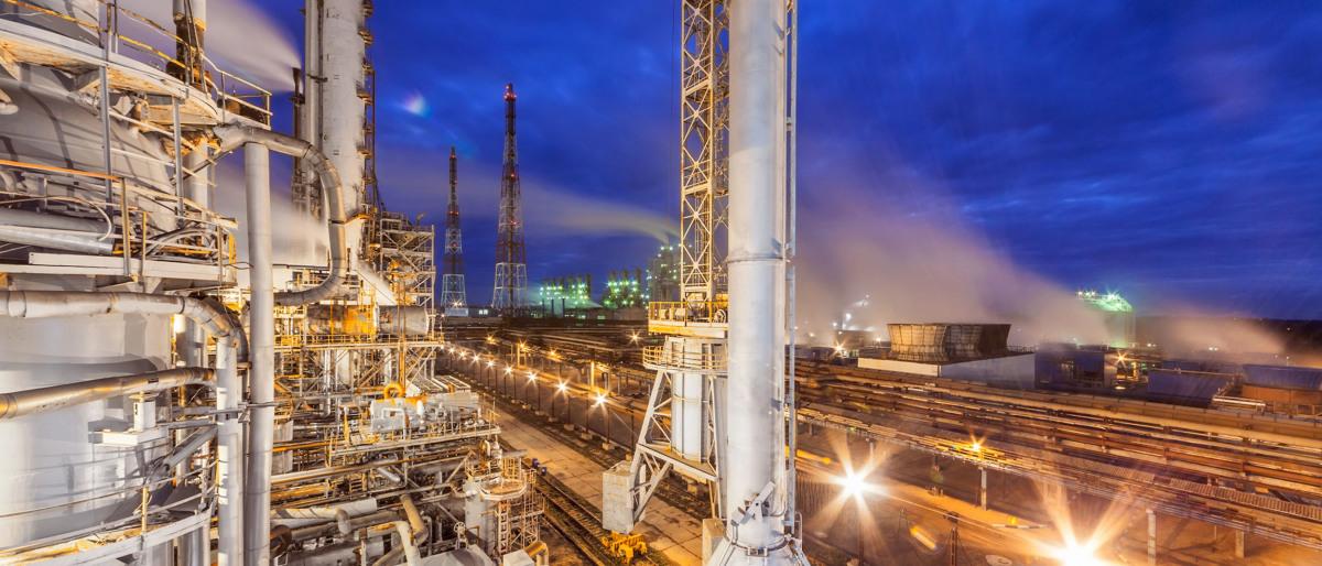 Industrieanlage mit Blick auf eine Bahnlinie bei Nacht