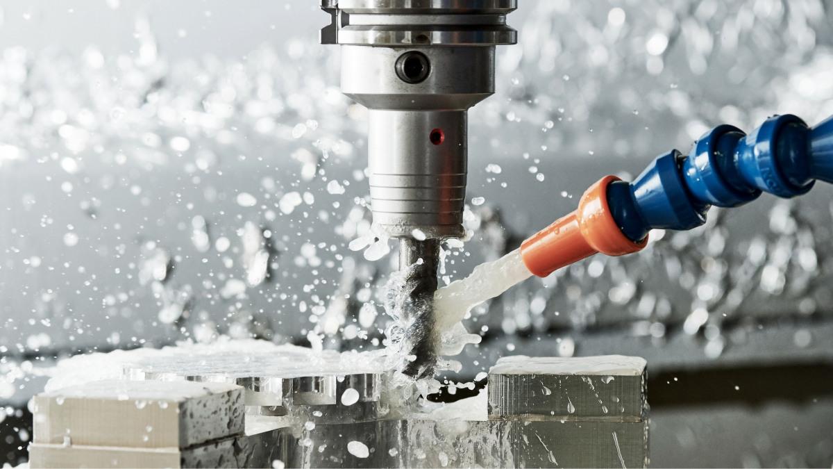 Maschinenbau: Ein Bohrer fräst sich in Metall. Anfallende Späne wir mit Wasser weggepült.