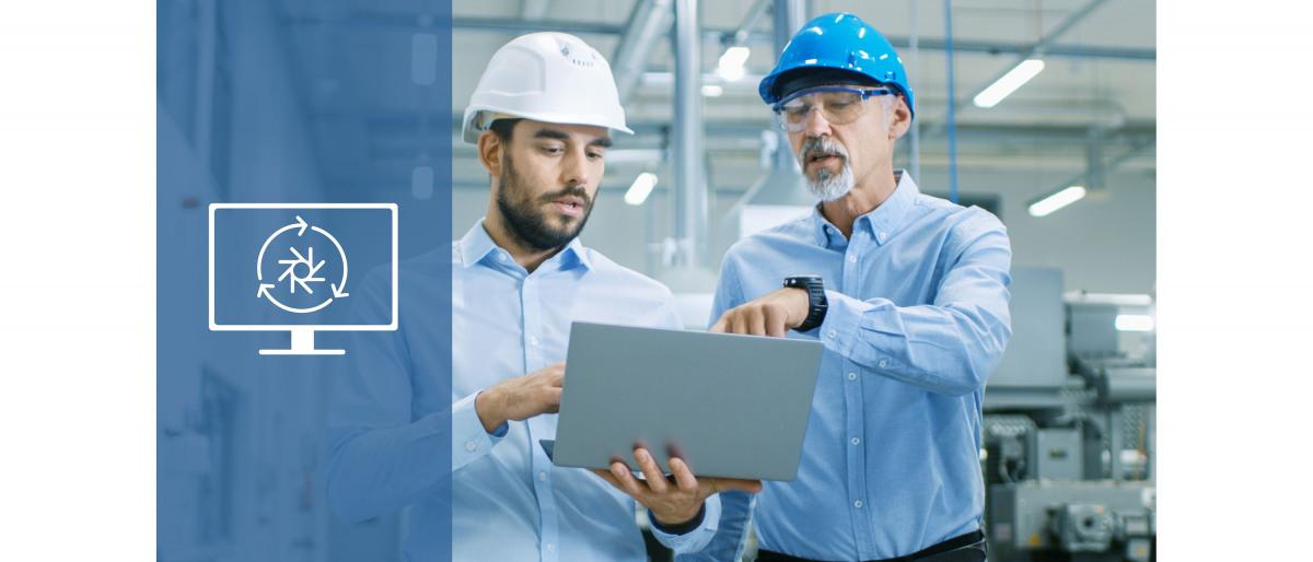 Zwei Kollegen schauen gemeinsam auf einen Laptop und sprechen über den Bildschirminhalt