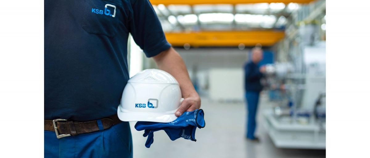 KSB Mitarbeiter hält einen Helm und Handschuhe