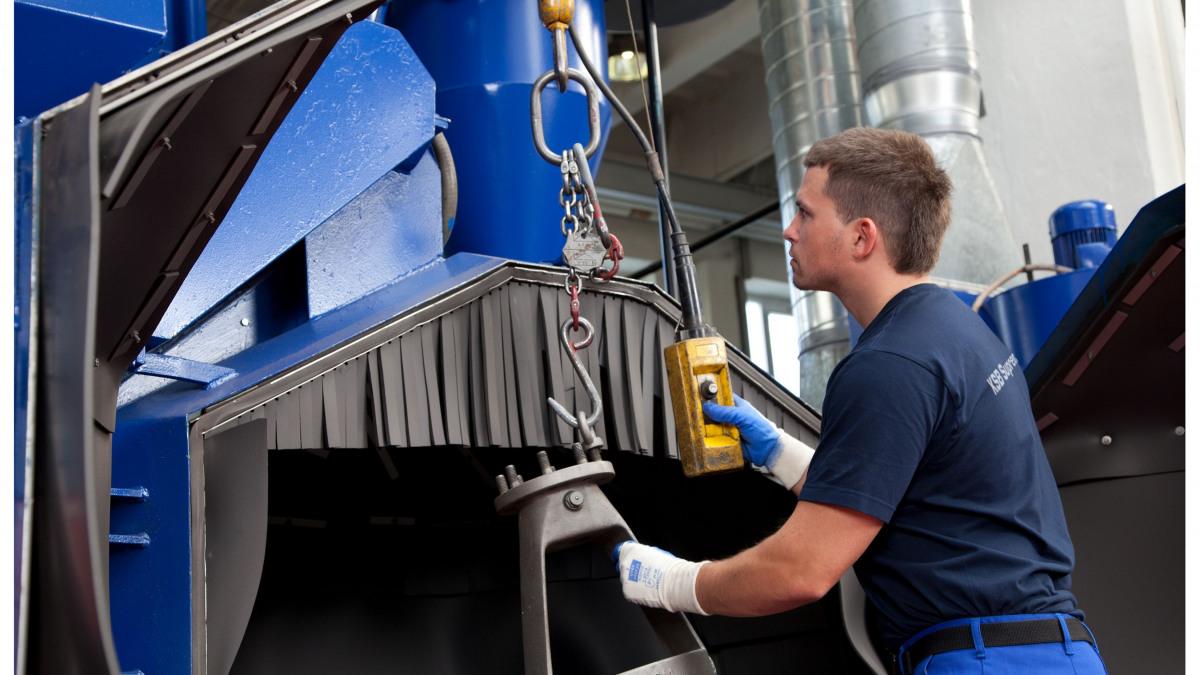 Servicemitarbeiter mit einem Armaturen-Oberteils vor der Sandstrahlmaschine
