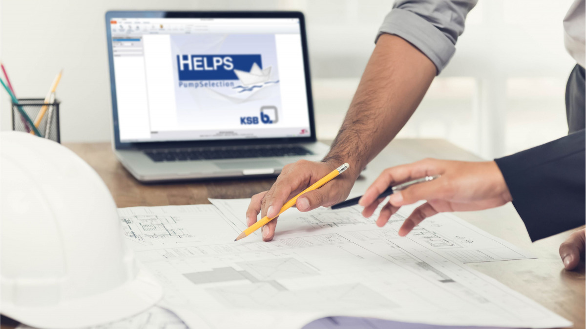 Hände mit Stiften über einem Arbeitspapier. Laptop im Hintergrund