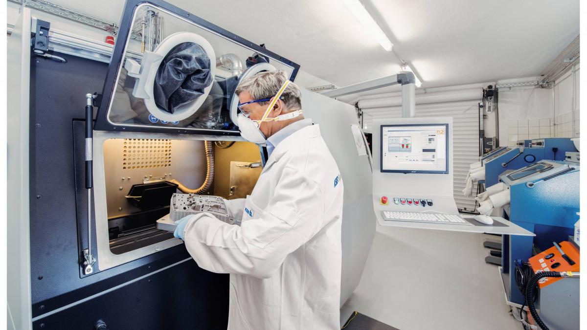 KSB-Mitarbeiter entnimmt additiv gefertigte Bauteile nach dem Laserschmelzen aus dem 3D-Drucker