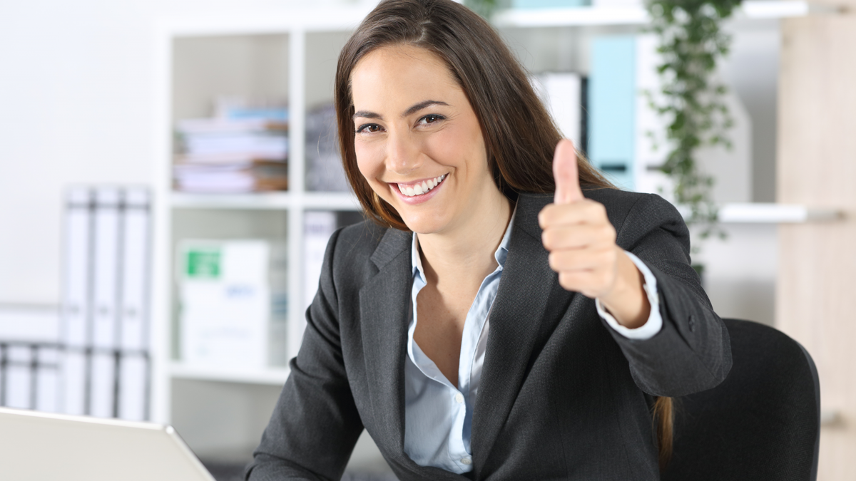 Female building services consultant working on laptop with thumbs up